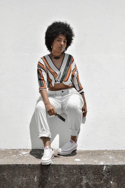 Стильная черная женщина возле цементной стены на улице