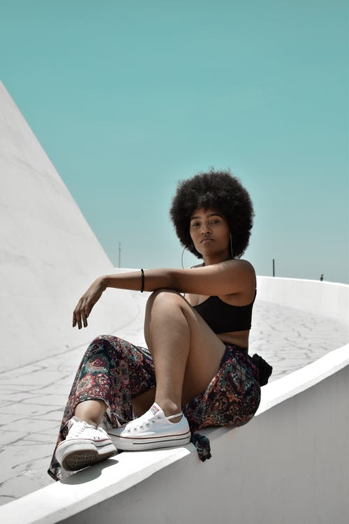 Young focused African American female in stylish wear with Afro hairstyle sitting on fence and looking at camera