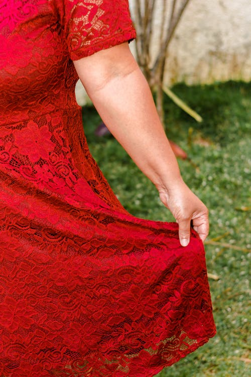 Crop woman in stylish red dress on lawn