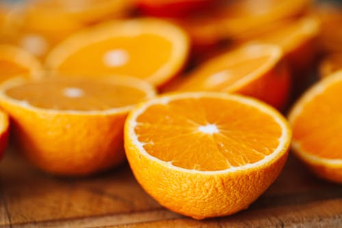Sliced Orange Fruits on Brown Wooden Table