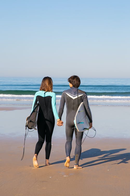 Couple Walking Barefoot on Sand