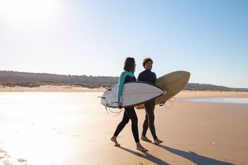 Couple Carrying Surfboards While Walking on Sand