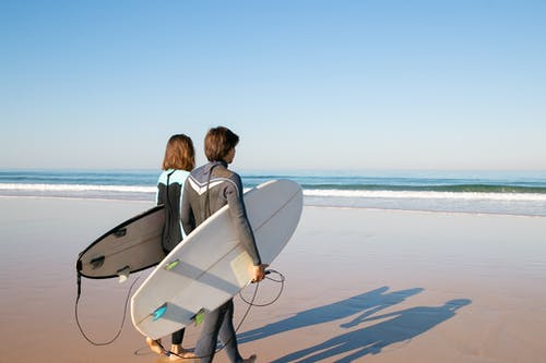 Woman in Black Jacket Carrying White Surfboard on Beach