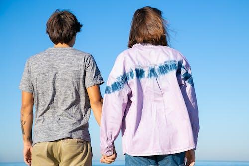 Couple Holding Hands Under Blue Sky