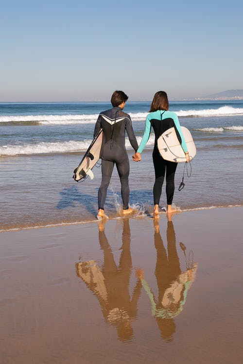 Couple Holding Hands While Walking on Shore