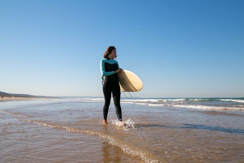 Woman in Blue and Black Wet Suit Carrying White Surfboard on Beach