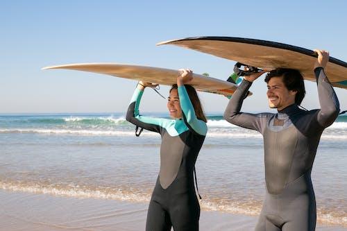 Man in Blue Dress Shirt Holding Brown Surfboard on Beach