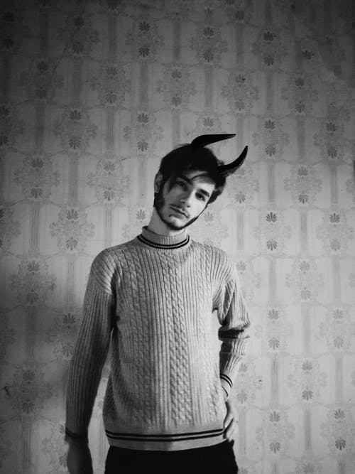 Man in Knitwear Wearing Headband with Horns