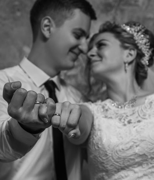 Black and white low angle of smiling loving couple in elegant outfits showing wedding rings to camera