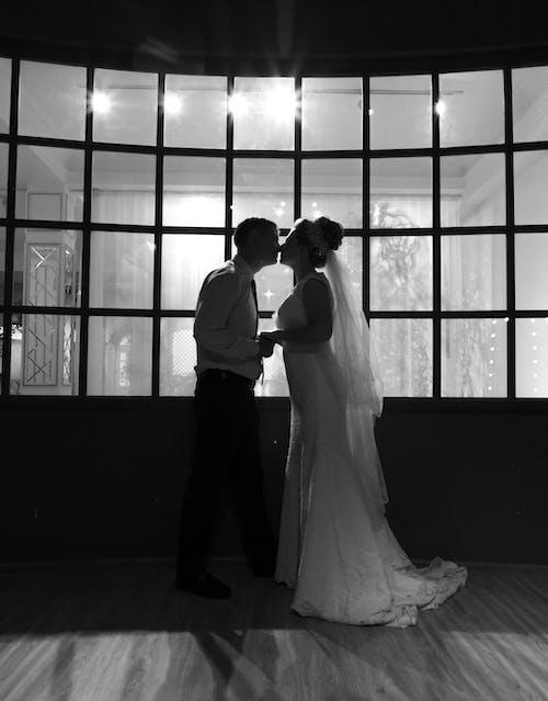Bride and groom kissing against window