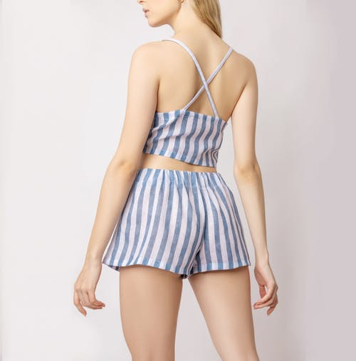 Back view of crop faceless slim woman in stylish striped top and shorts standing against white background