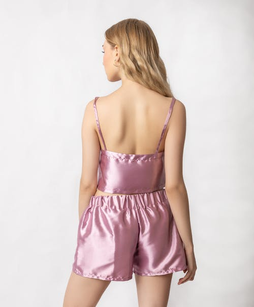 Back view of anonymous female wearing trendy pink silk sleepwear with bare back standing in studio