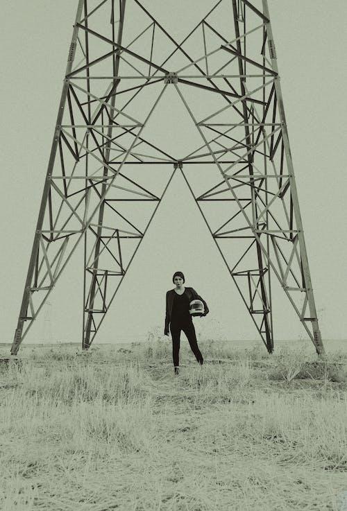 Trendy woman with helmet walking in field near metal tower