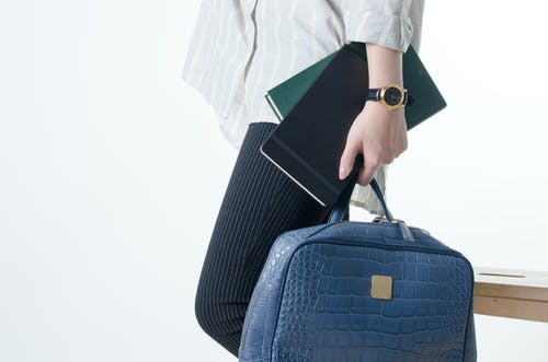 Hand with Notebooks and Blue Hand Bag