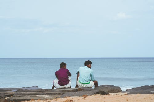 Men Sitting Together on Gray Rock Near Water