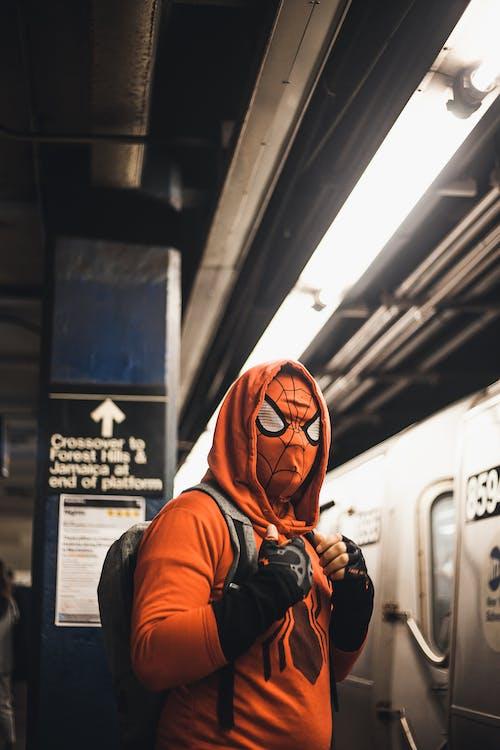 Man in Orange and White Hoodie Wearing Orange Mask