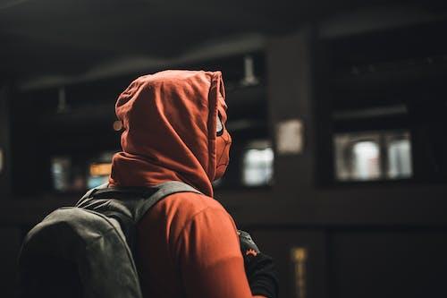 Person in Orange Hoodie and Black Denim Jeans