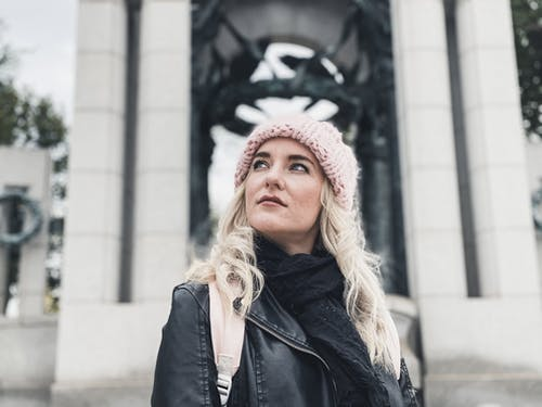 Woman in Black Leather Jacket Wearing Red and White Floral Knit Cap