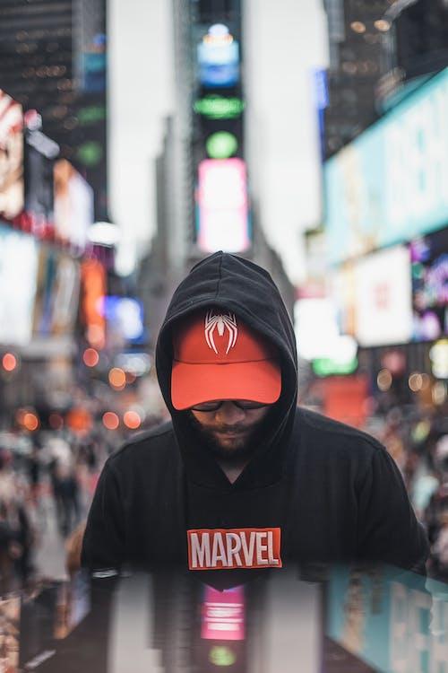 Man in Black and Orange Hoodie Wearing Black Knit Cap