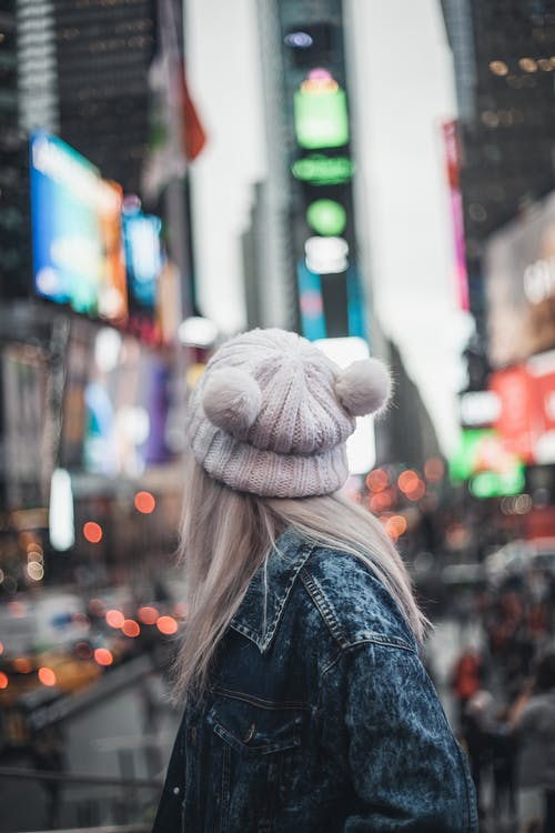 Woman in Blue Denim Jacket and White Knit Cap Standing on Street during Night Time