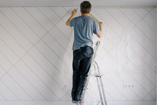 Faceless house painter undercoating wall in bright room