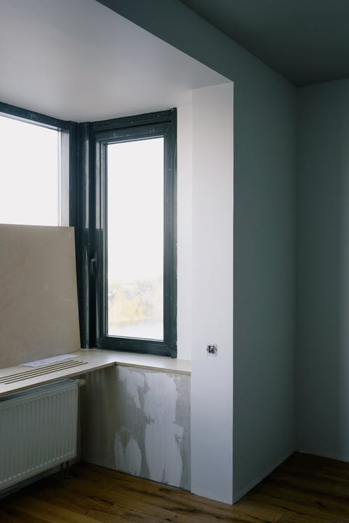 Long rectangular transparent window with thin black frame in bright room with white walls in new building