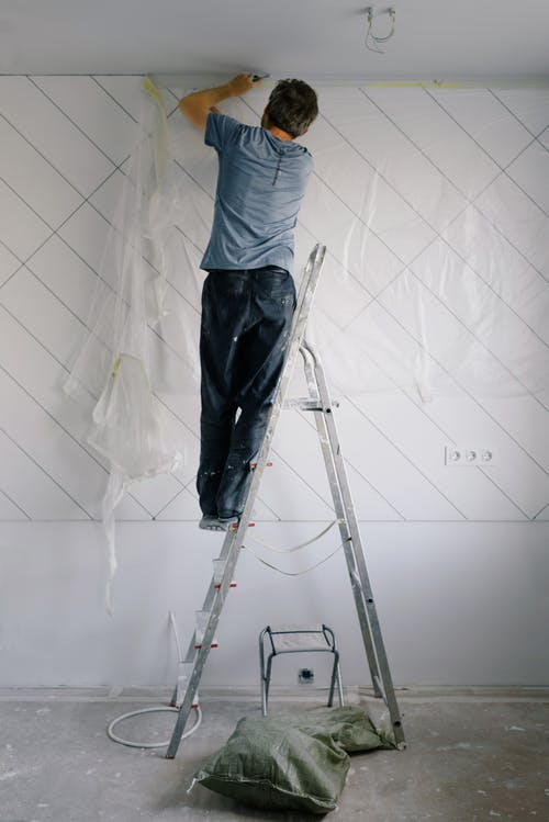 Housepainter on ladder working in room