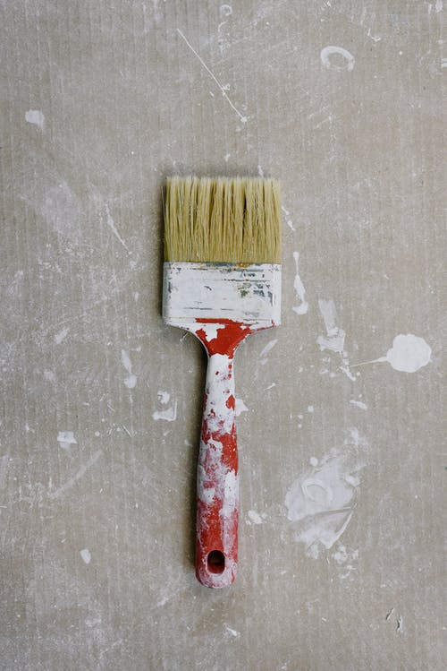 Messy paintbrush on dirty floor