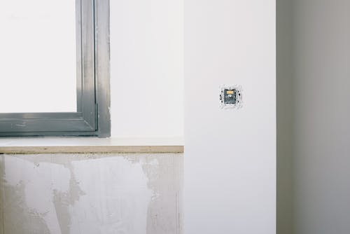 Repairs and installation of new electrical outlet on white wall near window in light apartment