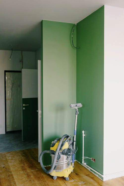 Building vacuum cleaner placed in corner of green painted room during renovation works in new apartment