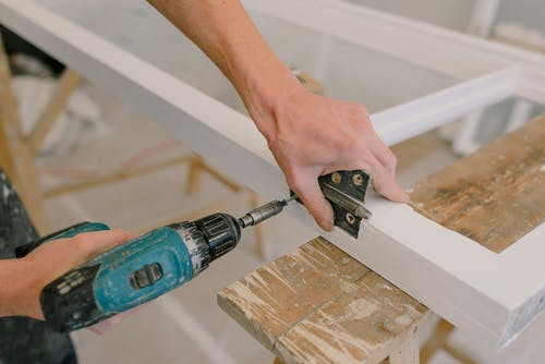 Unrecognizable professional male master using cordless screwdriver to install metal hinge on wooden window in light room during repair works
