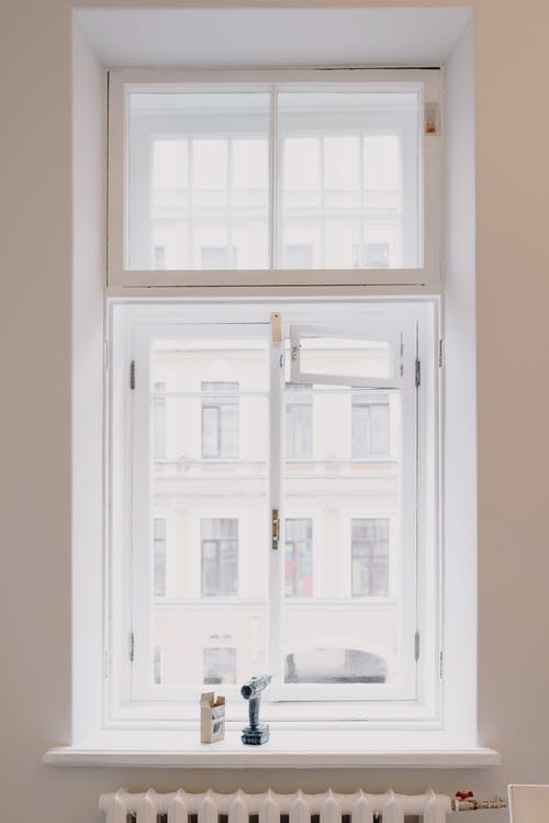 Wooden window with white frame overlooking building in city installed in light room with battery and screwdriver on windowsill in apartment
