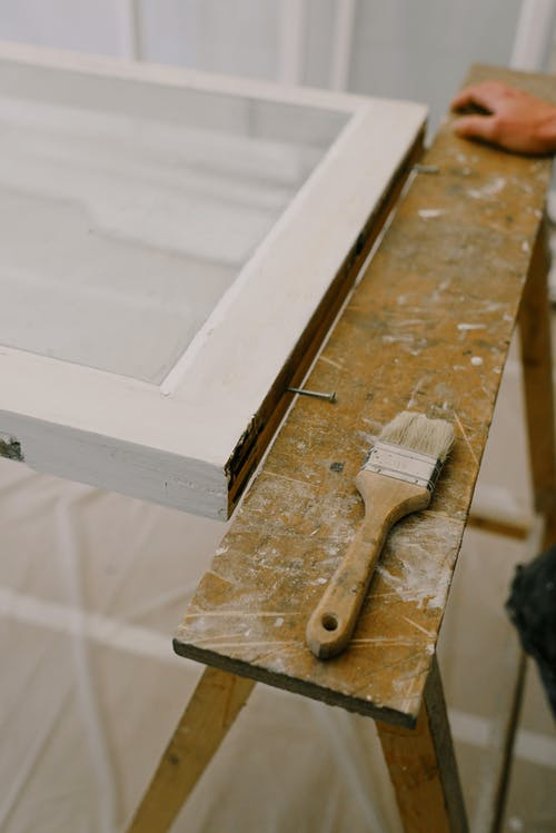 From above of anonymous craftsman standing near wooden workbench with brush and window with white frame in room during repair works