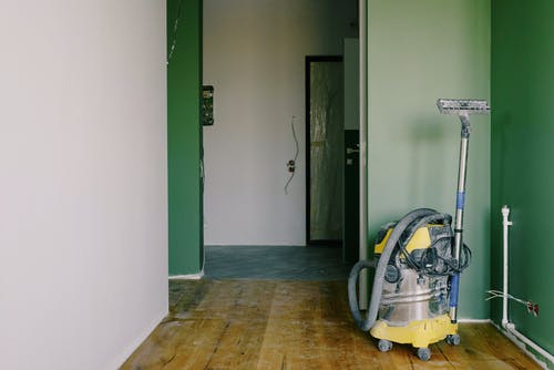 Industrial vacuum cleaner placed on dirty parquet in room with green walls and doorway in spacious apartment during repair works