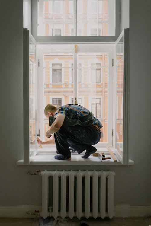 Anonymous man on windowsill during repair work