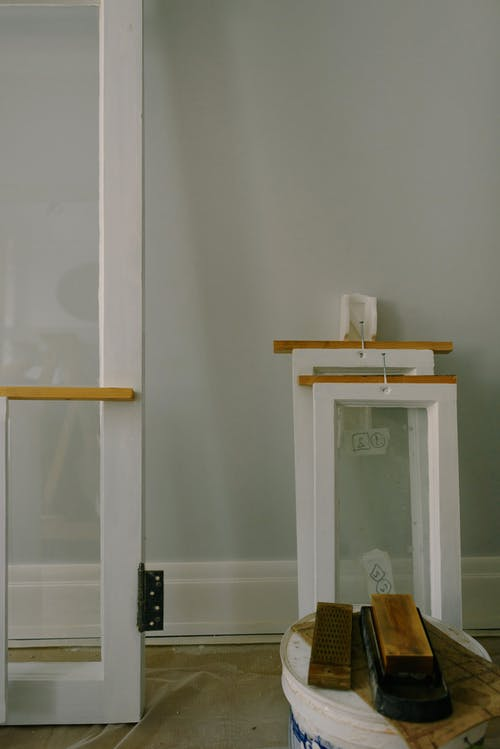 White window frames with hinge on floor with paint container in flat during renovation