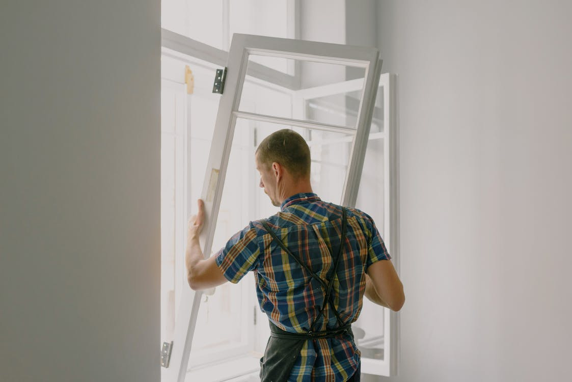 Unrecognizable workman installing window in house during renovation process