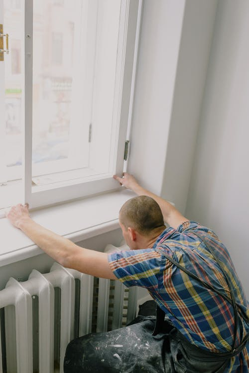 Back view of unrecognizable fitter in dirty apron installing window above radiator while doing home renovation