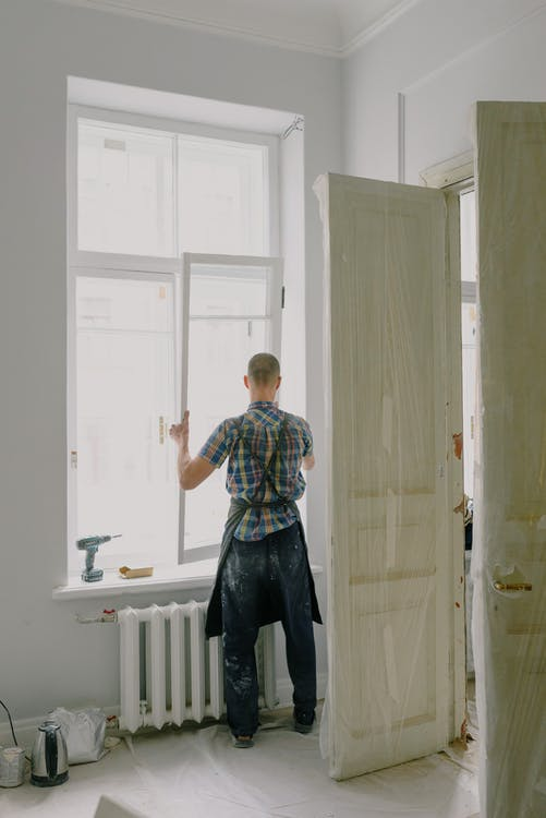 Faceless handyman mounting window in new house