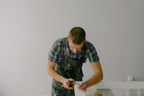 Concentrated anonymous joiner in apron working with wooden plank for furniture in light room