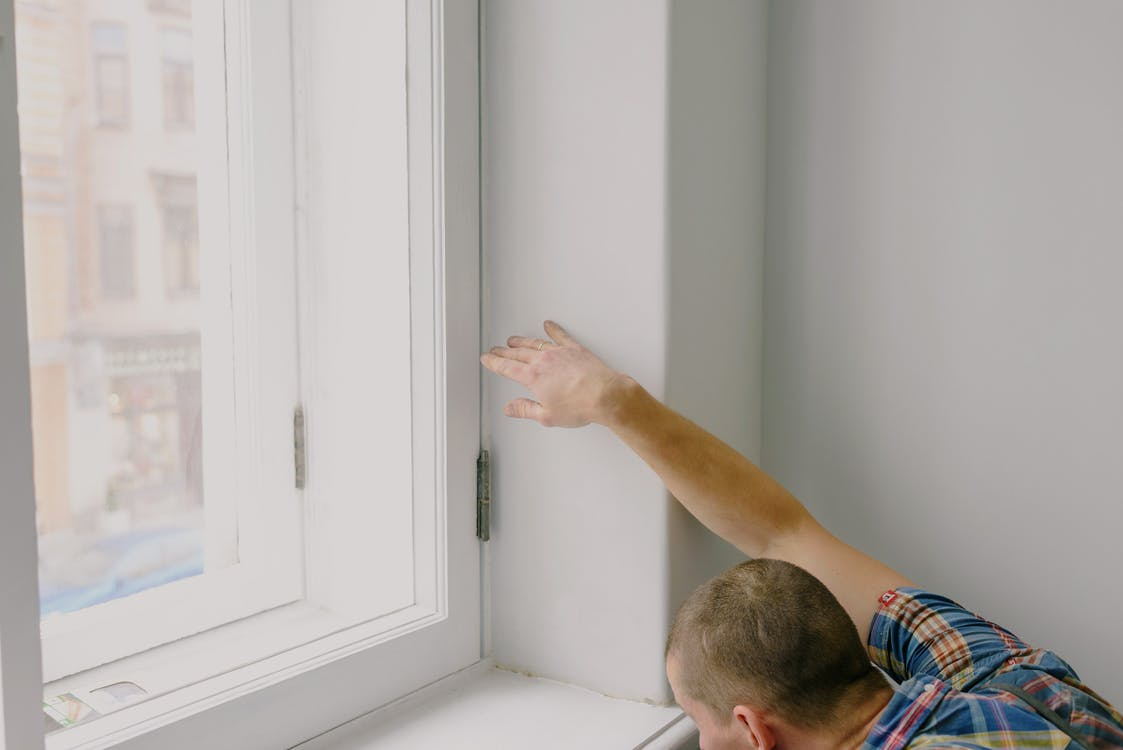 Man installing new window in apartment