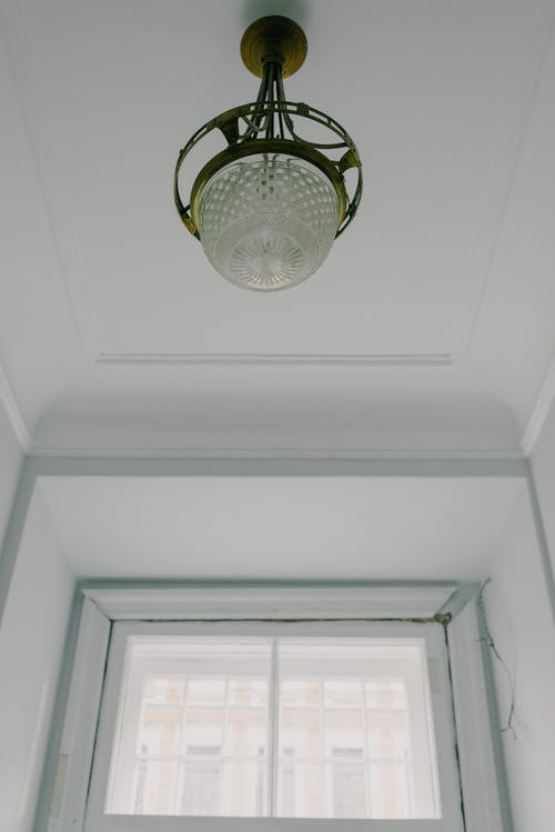 Frim below of ornamental retro lamp placed near window in light spacious room in daytime