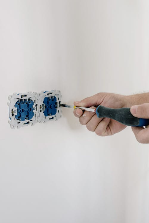 Electrician installing switches in light room