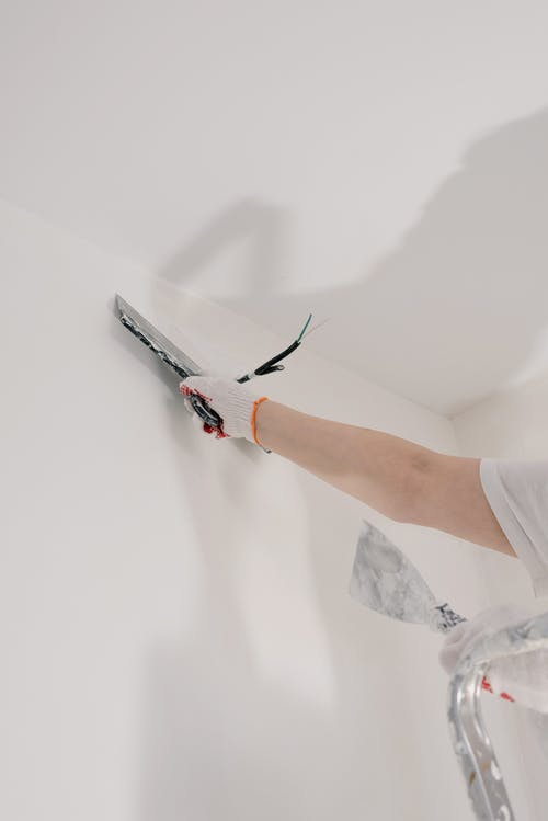 Crop unrecognizable male in gloves holding tool while standing on ladder and renovating walls in flat