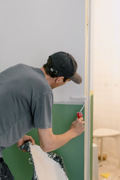 Man painting walls in new apartment