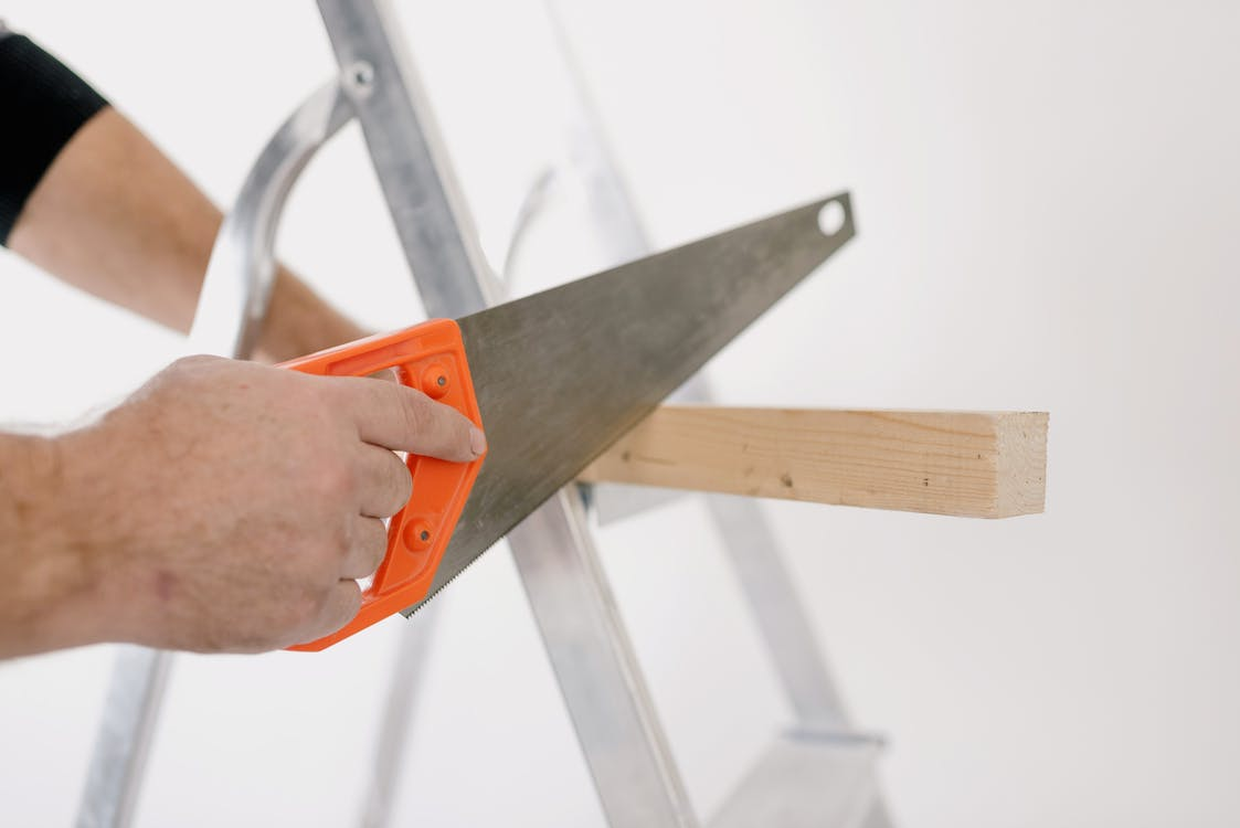 Crop man sawing wooden plank at home