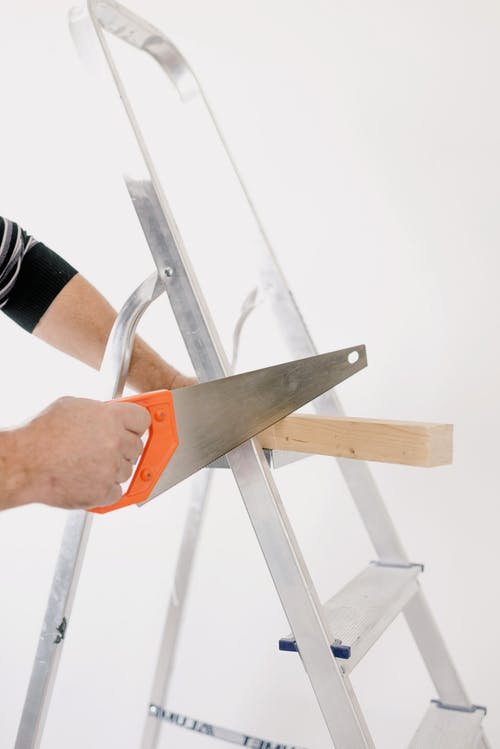 Crop man sawing wooden plank on ladder