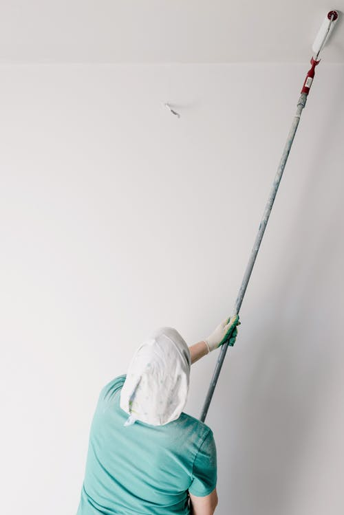 Back view of anonymous male worker with roller painting ceiling while working at home