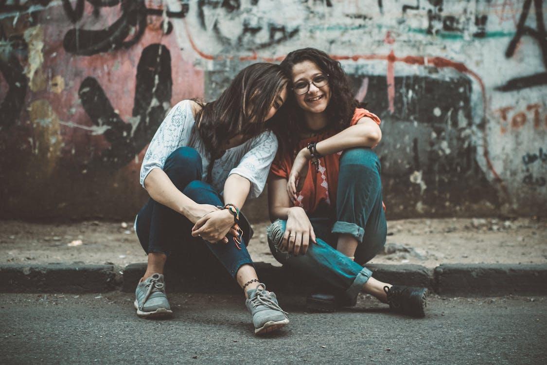 Two Women Sitting on Pavement Near Painted Wall