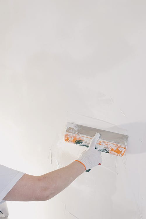 Crop man plastering wall at home